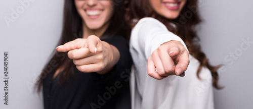 Photo  Smiling business women pointing at camera at gray background