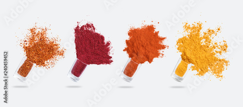 Fototapeta Glass jars with various spices flying on white background