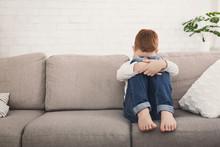 Boy Sitting On Sofa And Hug His Knee In Tear