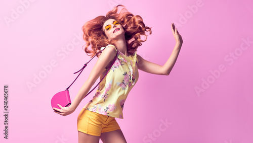 Obraz Portrait lovable woman having fun in studio wearing Stylish blouse, fashion yellow shorts, Trendy wavy hairstyle, makeup. Redhead model girl with happy positive emotion - fototapety do salonu