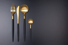Set Of Black And Gold Cutlery On Black Background