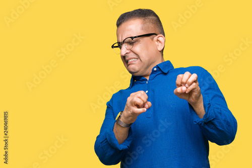Fotografie, Tablou  Middle age arab man wearing glasses over isolated background disgusted expression, displeased and fearful doing disgust face because aversion reaction