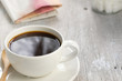 Coffee cup, cube sugar and newspaper is placed on the dining table in the morning. - image