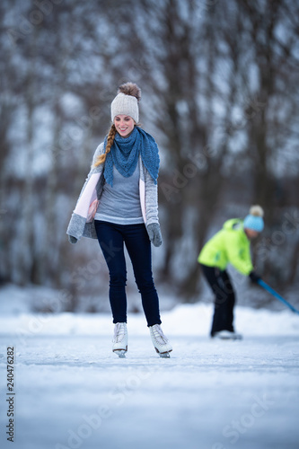 Fotografia  Young woman ice skating outdoors on a pond on a freezing winter day