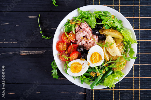 Healthy hearty salad of tuna, green beans, tomatoes, eggs, potatoes, black olives close-up in a bowl on the table. Salad Nicoise. French cuisine. Top view. Flat lay