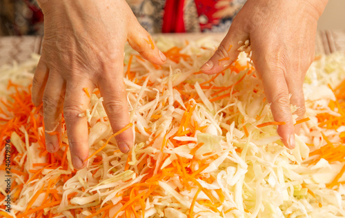 Woman salting cabbage with carrots in the kitchen