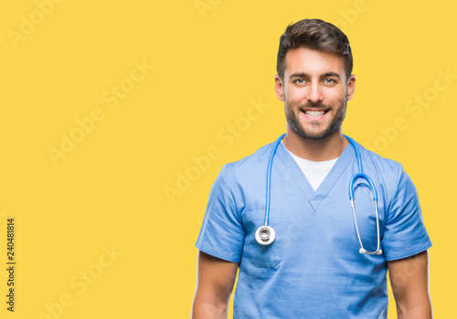 Cuadros en Lienzo  Young handsome doctor nurse man over isolated background with a happy and cool smile on face