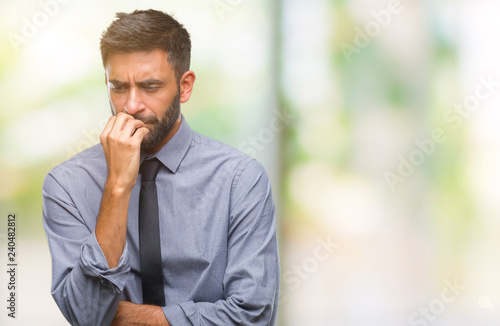 Stampa su Tela  Adult hispanic business man over isolated background looking stressed and nervous with hands on mouth biting nails