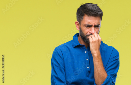 Fotografia  Adult hispanic man over isolated background looking stressed and nervous with hands on mouth biting nails