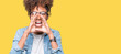 Leinwandbild Motiv Beautiful young african american woman wearing glasses over isolated background Shouting angry out loud with hands over mouth