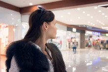 Close Up Of Young Brunet Girl In Shopping Mall Looking Away From The Camera. Good-looking Woman Stands In Shopping Centre Walking Area And Looks Into The Distance. Girl Looks For Something In Mall.
