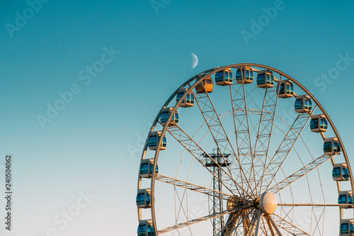 Photo  Helsinki, Finland. Moon Rising Above Ferris Wheel