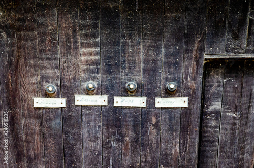 Fotografie, Obraz  doorbells on an aged wooden wall, Havana, Cuba
