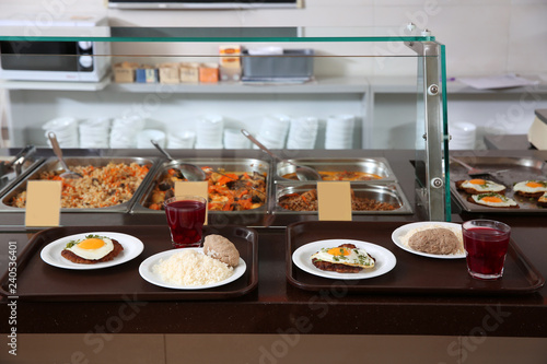 Trays with healthy food on serving line in school canteen