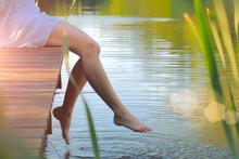 Swinging Bare Feet Of Woman Sitting On Pier. Summer Vacation