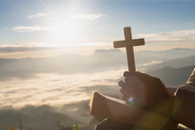 Hands Holding Wooden Cross Over Open  Holy Bible On The Mountain Background With Morning Sunrise, Spirtuality And Religion,  Worship, Sins And Prayer.