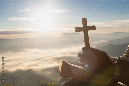 Photo Hands holding wooden cross over open  holy bible on the mountain background with morning sunrise, spirtuality and religion,  Worship, sins and prayer