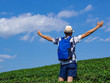 Young asian backpacker traveling into tea fields. Young man traveler take a photo of mountain tea field with blue sky background. Freedom Concept.
