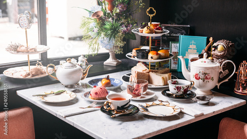 Fototapeta English afternoon tea set including hot tea, pastry, scones, sandwiches and mini pies on marble top table. obraz