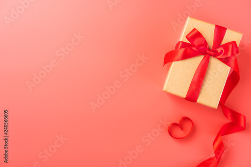 Fotografía  Gift box with red ribbon in trendy color of 2019 living coral background, concept of Valentine's, anniversary, mother's day, copy space, top view