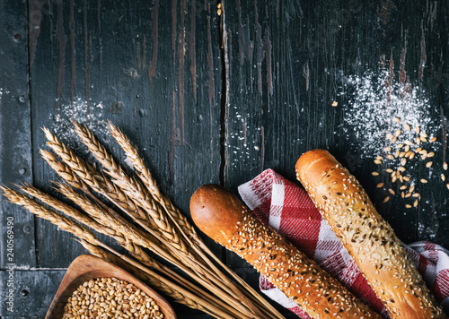 Staande foto Brood Fresh french baguette bread, organic flour and wholegrain wheat on dark vintage wooden board form above.