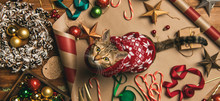 Getting Ready For Christmas Or New Year Holiday. Flat-lay Of Decorations, Ribbons, Gift Paper, Door Wreath, Glittering Balls, Candy Canes And Cat In Christmas Sweater ,top View, Wide Composition