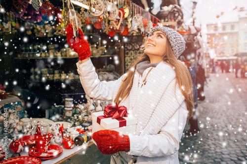 Fototapeta Smiling girl choosing decorations at Christmas market