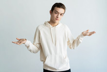 Uncertain Teen Boy Throwing Up Hands And Looking At Camera. Young Guy Doubting. Confusion Concept. Isolated Front View On White Background.