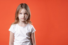 Portrait Of A Sad Little Girl Over Red Background.