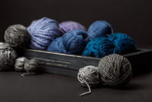 Close Up View Of Grey, Purple And Blue Knitting Clews In Wooden Box On Black Background