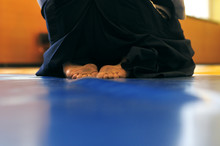 Aikido Background. A Man Sits In Zazen On A Blue Wrestling Mat. In White Kimano And Black Hakame. Web Banner With Place For Text. Without Faces And Recognizable Objects.