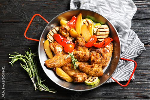 Wok with barbecued chicken wings and garnish on wooden background, top view