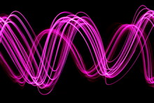 Long Exposure, Light Painting Photography. Pink Wavy Streaks Of Vibrant Light Against A Black Background