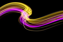Long Exposure, Light Painting Photography. Pink And Gold Neon Streaks Of Vibrant Color Against A Black Background