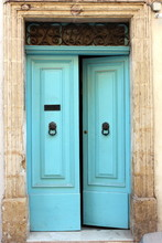 Turquoise Blue Doors, Slightly Ajar, With Black Iron Metalwork Knocker And Letterbox, And Limestone Brickwork