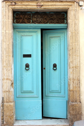 Photo Turquoise blue doors, slightly ajar, with black iron metalwork knocker and lette