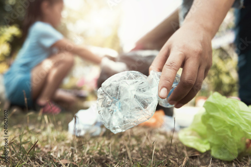 Photographie  woman hand picking up trash bottle for cleaning at park