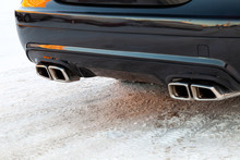 Close-up Of A Black Luxury Car Bumper Of A Mercedes Benz Brand Sedan VIP Class With Turbo Exhaust Pipes Outdoors In The Winter On The Snow.