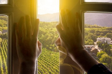 window to the new life, hands open window with gorgeous landscape nature view on summer