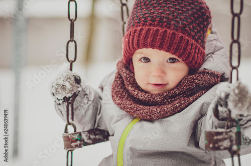 portrait funny little child girl wearing in red hat, a scarf, and a warm winter suit with gloves having fun at winter day riding on a swing on playground