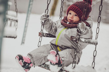 Funny Little Child Girl Wearing In Red Hat, A Scarf, And A Warm Winter Suit With Gloves Having Fun At Winter Day Riding On A Swing On Playground
