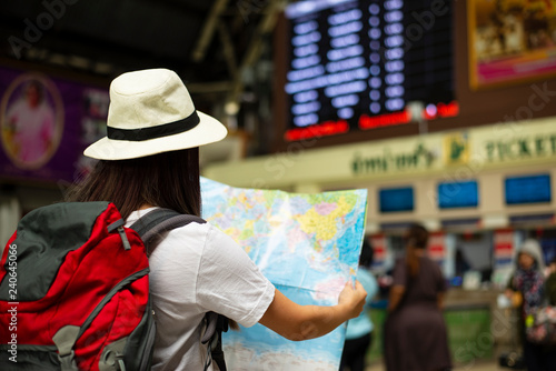 Photo sur Toile Hong-Kong Young traveler tourist woman covering with paper map, search route, at international airport or train station,Young woman traveler with backpack at train railway train station
