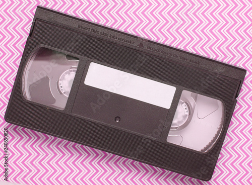 Fotografering  Video cassette on blue creative background, media 80s. Top view..
