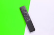 canvas print picture - A modern TV remote control on green white background. Top view, minimalism.