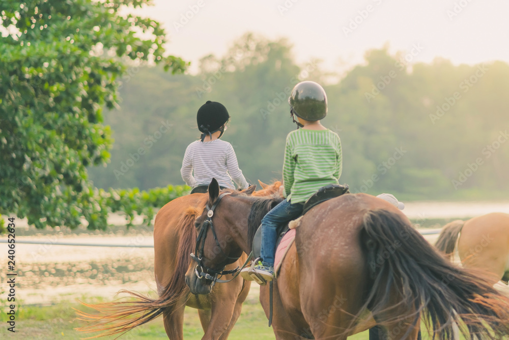 Fototapety, obrazy: Kids learn to ride a horse near the river before sunset.