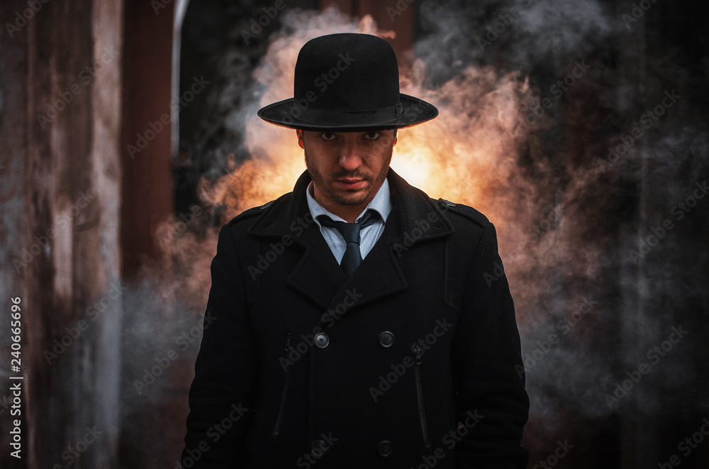 Fototapeta Young handsome man wearing black hat and classic suit and tie
