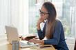 Pensive pretty Vietnamese woman in glasses reading information on laptop screen