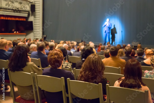 Obraz na plátně  Man appears on stage in theater with many people