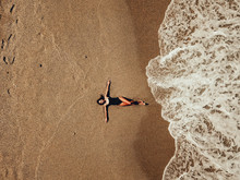Aerial Top View Young Woman Lying On The Sand Beach And Waves