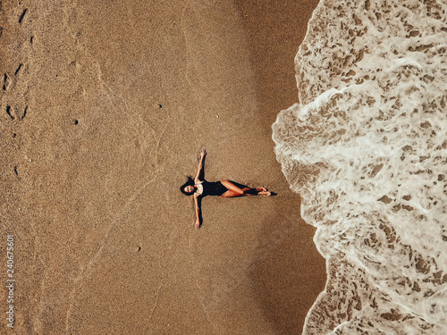 Fotografie, Obraz  Aerial top view young woman lying on the sand beach and waves